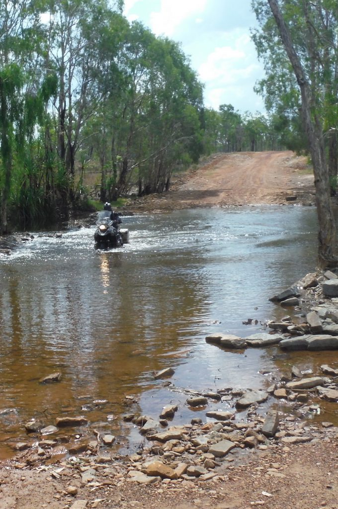 Adventure motorbike riding through a river crossing in Northern Territory