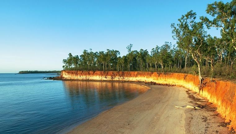 Sandstone cliffs next to a sandy beach in Garig Gunak Barlu National Park in the Coburg peninsula, Northern Territory