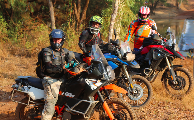 On tour with Southern Cross Motorbike Tours. 3 motorbike rders A stopped by a river in the Northern Territory.