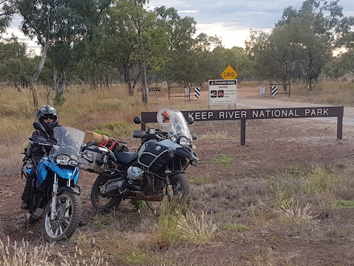 Two motorbikes parked by the sign to the Keep River National Park, Northern Territory