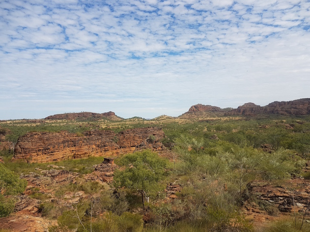 View of across a plain to a rocky escarpment at the Keep River National Park