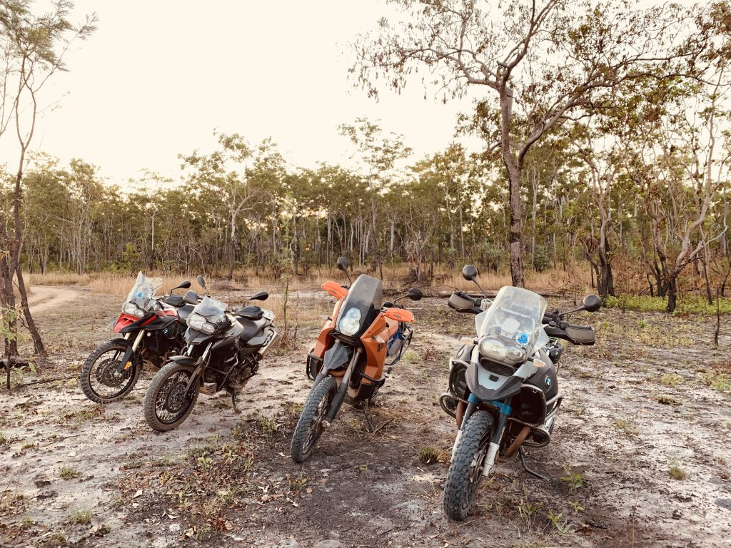 Four motorbikes on tour, parked beside trees on a sandy road in the Northern Territory
