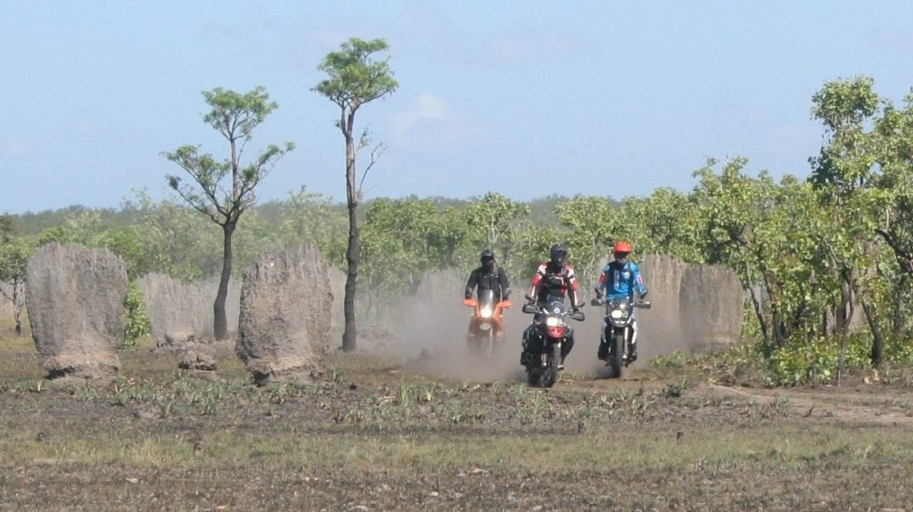 Three adventure motorbike riders along a dusty track next to magnetic termite mounds in the Northern Territory